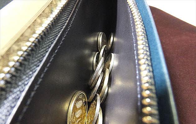 黒いヌメ革とコインの写真