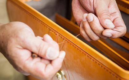 職人が一張り 一張り縫製する写真