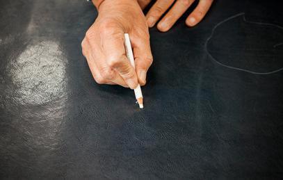 職人が革をチェックする写真