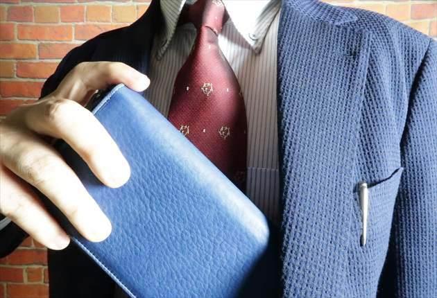 スクモレザー ラウンドジップ長財布を持つ財布課長レオンの写真