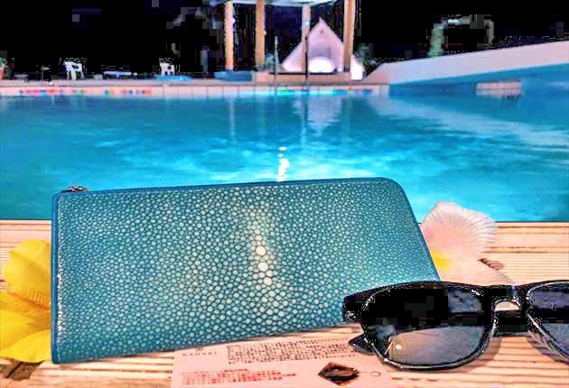 夜のプールサイドで写したBAHARI長財布L字ファスナーポリッシュターコイズブルーの写真
